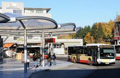 Poppenbüttler Busbahnhof - Busumsteigeanlage Architekten Blunck + Morgen. Ein Bus Richtung U/S Ohlsdorf fährt gerade ab. Fahrgäste stehen an der Haltestelle.