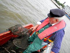 Der Fischer holt die ausgelegte Reuse in seine kleine Jolle.