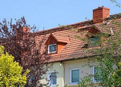 Dachfenster zwischen Bäumen und Sträuchern - Gartenstadt Steenkampsiedlung HH-Bahrenfeld.