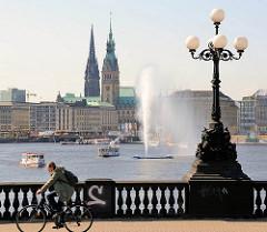 Blick über die Hamburger Lombardsbrücke zur Binnenalster - Alsterschiffe / Alsterdampfer auf dem Wasser - Alsterfontaine; Turm vom Hamburger Rathaus und der Nikolaikirche.