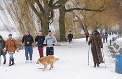 Spaziergaenger am Alsterufer im Winter. Schnee liegt auf dem Weg.