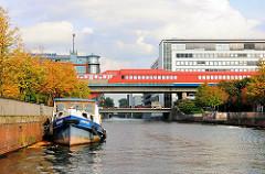 Blick in den Mittelkanal; eine Barkasse liegt an der Kaimauer - im Hintergrund fährt eine S-Bahn in den Bahnhof der Haltestelle Hammerbrook ein.