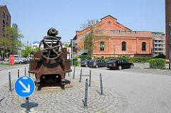 Altes Maschinenteil auf dem Gelände des ehem. Gaswerks Bahrenfeld - im Hintergrund die Industriearchitektur der Reinigerhalle Nord.
