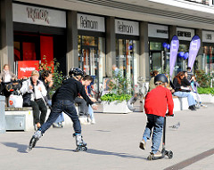 Kinder mit Roller Skates und Tretroller auf dem Marie Jonas Platz in Hamburg Eppendorf -