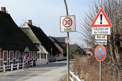 reetgedeckte Häuser in Kirchwerder - Fahrradfahrer in der 30er Zone.