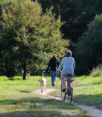 Hundeauslaufzone im Niendorfer Gehege - Frauen führen ihre Hunde auf einer Wiese aus. Fahrradfahrerin mit Hund auf dem Weg im Wald.