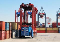 Ein Portalhubwagen transportiert einen Container auf dem Gelände des Terminals EUROGATE - im Hintergrund ein Frachter am Predöhlkai.