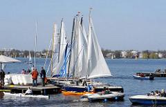Segelboote unter Segel am Bootssteg - Tretboote fahren auf der Alster - Alsterufer des Hamburger Stadtteil St. Georg
