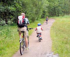 Fahrradausflug ins Naturschutzgebiet Raakmoor in Hamburg Hummelsbüttel - Fahrradfahrer mit Kinder auf einem Wanderweg durch das Naturschutzgebiet.