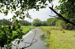 Lauf der Bille zwischen Feldern und Bäumen als Grenzfluss der Stadtteile Hamburg Lohbrügge und Billwerder.