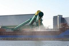 Verladung von Schüttgut auf einen Frachter - die Abdeckung des Laderaums ist geöffnet über eine Transportanlage wird das Schiff beladen. Motive aus den Hamburger Stadtteilen - Bilder aus Hamburg Wilhelmsburg.