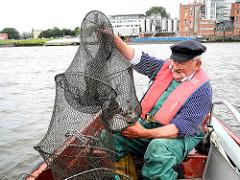 Der Hafenfischer betrachtet seinen Fang in der Reuse.
