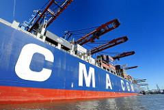 Bordwand mit den Buchstaben CMA CGM der Reederei der CALLISTO - die Containerkräne des Hamburger Terminals Burchardkai ragen über das 46m breite Schiff.
