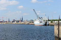 Ein Frachtschiff liegt am Versmannkai des Baakenhafens - im Hintergrund das Panorama der Hansestadt Hamburg.