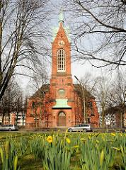 Turm der Hamburger Heiligengeistkirche am alten Dorfplatz des ursprünglichen Barmbeks - Osterglocken / Narzissen blühen auf der Wiese. ( 2005 )