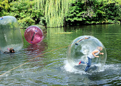 Kinderspass auf dem Schlossteich in Hamburg Bergedorf - in einem Megaball / Wasserkugel laufen Kinder über das Wasser.