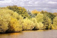 Herbststimmung am Ufer des Schleusengrabens im Hamburger Stadtteil Bergedorf - die Bäume am Ufer des Kanals stehen dicht zusammung und sind bunt herbstlich gefärbt.