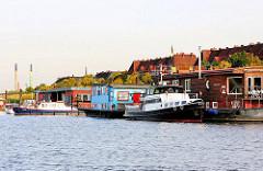 Spreehafen in Hamburg Wilhelmsburg - Hausboote und Arbeitschiffe sind an den Pontons vertäut - im Hintergrund Wohnhäuser in Hamburg Wilhelmsburg.