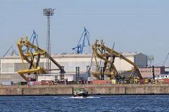 Kransprengung im Hamburger Kaiser Wilhelm Hafen - die hohen gelben Hafenkräne werden mit einer Sprengladung zu Fall gebracht. Bilder aus dem Hamburger Stadtteil Steinwerder, Hamburger Hafengebiet.