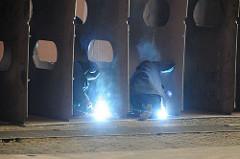 Werftarbeiter / Schweisser schweissen Stahlspanten für einen Schiffsrumpf zusammen.
