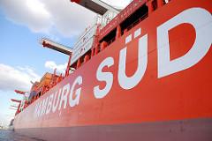 Schriftzug der Reederei HAMBURG SÜD an der roten Bordwand eines ihrer Schiffe, das im Hamburger Hafen beladen wird.