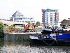 Blick von der Bille / Billekanal auf eine Kaianlage in Hamburg Rothenburgsort. Binnenschiffe haben am Ufer festgemacht - im Hintergrund Hochhäuser.