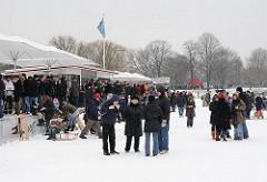 Winterfest in Hamburg bei zugefrorener Alster - Glühweinstand am Bootsanleger vor HH- St. Georg. Die HamburgerInnen stehen auf dem Eis und geniessen das heisse Getränk.
