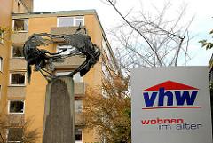 Schild vhw - WOHNEN IM ALTER - Metallskulptur Vögel auf Stele am Eingang des Seniorengebäudes in Hamburg Dulsberg.