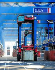 Ein Portalhubwagen nimmt einen Container am Burchardkai im Hamburger Hafen auf.