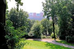 Blick vom Elbberg Höhe Neumühlen durch die Bäume Richtung Elbe - ein Containerschiff läuft in den Hamburger Hafen ein - die hoch gestapelten Container sind zwischen den Bäumen zu erkennen.