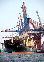 Ein Containerschiff legt vom Kai des Containerterminals ab - die Containerbrücken sind hochgefahren.