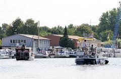 Zwei Motorboote haben gerade die Tatenberger Schleuse passiert und fahren auf der Dove-Elbe am Sportboothafen in Hamburg Moorfleet vorbei.