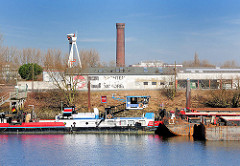 Blick über den Peutehafen - ein Schubschiff und Lastkähne, Schuten liegen am Ufer; im Hintergrund der historische Wasserturm in Hamburg Rothenburgsort auf der gegenüber liegenden Seite der Norderelbe.
