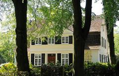 Alte hohe Bäume im Vorgarten einer Villa mit gelber Fassade in Hamburg Osdorf.