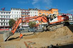 Bauarbeiten auf dem Spielbudenplatz - ein Bagger auf einem Sandhaufen, im Hintergrund Häuser an der Reeperbahn.