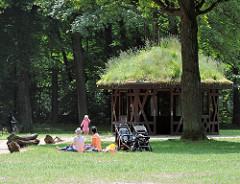 Spielplatz im Altonaer Volkspark von Hamburg Bahrenfeld - Mütter haben die Kinderkarren geparkt - Holzpavillon, das Dach ist mit Gras bewachsen.