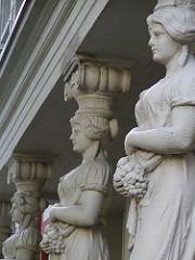 weibliche Skulpturen mit Weintrauben tragen als Säule einen Balkon in der Winterhuder Preystrasse.