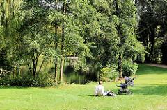 Fotos aus Hamburg Eimsbüttel - Grünanlage am Weiher - Vater mit Kleinkind und Kinderwagen im Gras in der Sonne.
