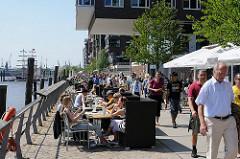 Restaurant in der Hamburger Hafencity am Dalmannkai - die Gäste sitzen am Wasser - Spaziergänger gehen Richtung Marco Polo Terrassen.