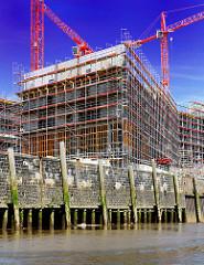 Kaimauer  im Hamburger Baakenhafen / Versmannkai bei Ebbe; die Kaianlage ist auf Holzstämmen gegründet - Streichdalben schützen die Wand / Schiffe beim Anlegen. Baustelle mit Kränen in der Hafencity.