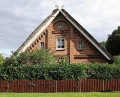 Backsteinfassade eines ländlichen Gebäudes mit Reet gedeckt.