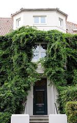 Mit Kletterpflanzen bewachsener Hauseingang und Erkerturm - Immergrünes Geissblatt an der Hausfassade - Wohngebäude Hamburg Heimfeld.
