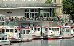 Fahrgastschiffe der weissen Alsterflotte am Jungfernstieg. Auf der Terrasse des Alsterpavillons sitzen die Gäste und blicken auf den Hamburger See.