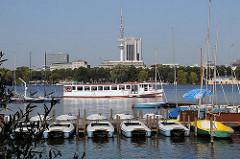 Bootsverleih an der Alster - Tretboote liegen am Bootssteg - ein weisses Schiff der Alsterflotte fährt Richtung Uhlenhorst. Im Hintergrund das Alsterufer von Hamburg Harvestehude, sowie der Fernsehturm und das Radisson Hotel Hamburg