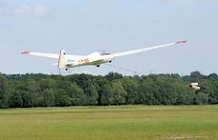 Start eines Segelflugzeugs - das Flugzeug wird von der Winde hochgezogen und schwebt über der Startwiese des Boberger Segelflugplatzes in Hamburg Lohbrügge.