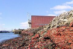zerstörte Ziegelmauer am Kai des Grasbrookhafens - im Hintergrund der Kaispeicher A.