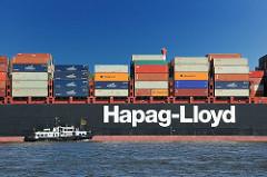 Schriftzug der Reederei Hapag-Lloyd - das Lotsenschiff 1 fährt lägsseits des mit Container beladenen Frachtschiffs.