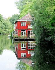 Idyll am Ufer des Isebekkanals - Holzhaus mit roter Fassade am Kanalufer - Spiegelung im Wasser; Bilder aus HH-Eimsbüttel.