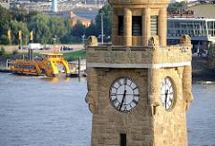 Historischer Uhrenturm der St. Pauli Landungsbrücken - auf der gegenüber liegenden Elbseite der Anleger mit Hafenfähre zum Musical König der Löwen.