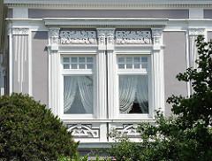 Jugendstildekoration an der Fassade eines Wohnhauses  in Hamburg Blankenese - weiss abgesetzer Bauschmuck.